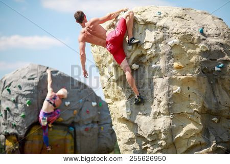 Photo from back of strong sporty man in red shorts and woman on workout at climbing boulders against blue sky with clouds