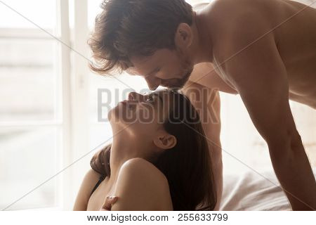 Romantic Couple Looking In Eyes Enjoying Romantic Moment In Bed