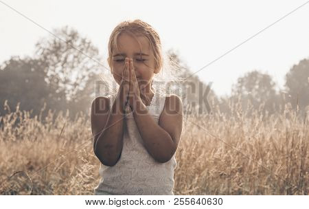 Little Girl Closed Her Eyes, Praying Outdoors, Hands Folded In Prayer Concept For Faith, Spiritualit