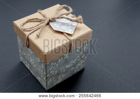 Kraft gift box on a dark contrasted background, decorated with a textured bow and feathers, creating
