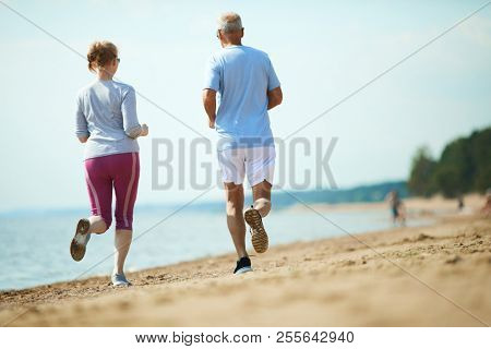 Back view of senior couple in activewear running along coastline on sandy beach