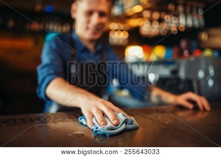 Barman in apron cleans bar counter after party