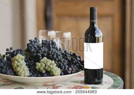 Blank Label On A Red Wine Bottle Besides A Bunch Of Grapes