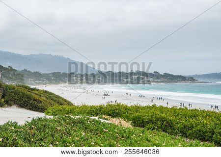 CARMEL-BY-THE-SEA, USA - May 13 2018: People enjoying a day on a tropical beach at Carmel-by-the-Sea, California on an overcast summer day in a scenic view of the Pacific Ocean and coastline