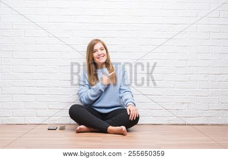 Young adult woman sitting on the floor in autumn over white brick wall cheerful with a smile of face pointing with hand and finger up to the side with happy and natural expression on face