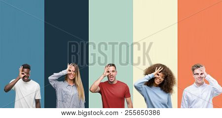 Group of people over vintage colors background doing ok gesture with hand smiling, eye looking through fingers with happy face.