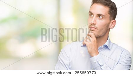 Handsome young businessman with hand on chin thinking about question, pensive expression. Smiling with thoughtful face. Doubt concept.