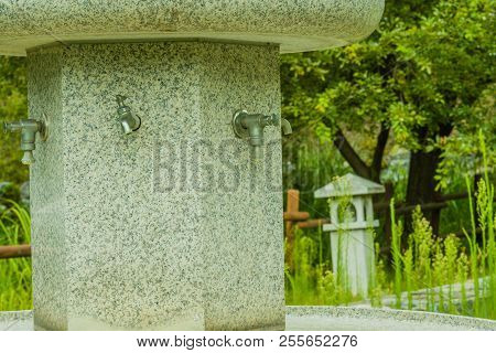 Large hand washing water fountain in a public park with lush green foliage. poster