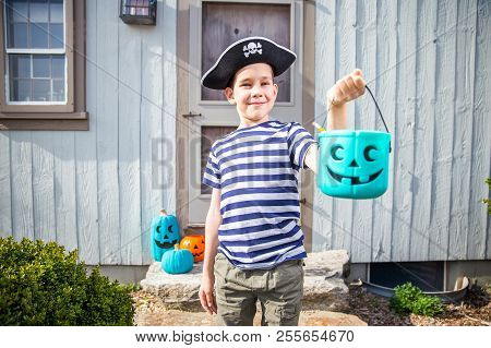 Child In A Pirate Costume Holding A Teal Bucket. Trick-or-treating. Teal Pumpkin. Alternative Non-fo