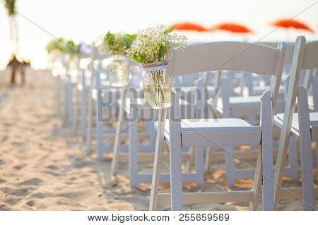 Wedding Ceremony On The Beach. White Flowers In A Mason Jar At A Wedding Ceremony. Empty Decorated C