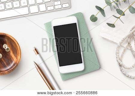 bright feminine styled desk with computer keyboard, writing supplies, eucalyptus twigs and a white smartphone mock-up with blank screen, flat lay / top view