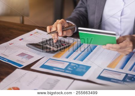 Businesswoman Using Calculator To Calculate Saving Account Passbook And Statement With Financial Rep