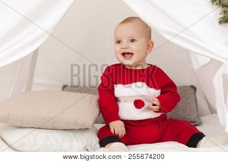 Lovely Baby In Red Clothing Smiling And Looking Away While Sittng In Small Tent Decorated With Conif
