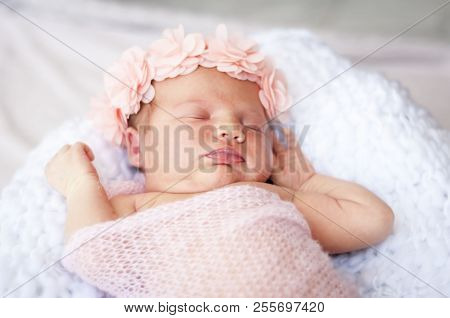 Cute Caucasian Newborn Infant Baby Girl Asleep. Pink Flower Band On Her Head And Pink Plaid. Adorabl