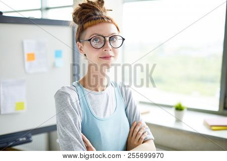 Ambitious confident hipster startupper with short fringe smiling at camera and crossing arms on chest in office