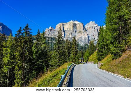 The beautiful sunny day. The road passes in the coniferous forests in limestone and dolomite rocks. Dolomite Alps. The concept of active, extreme and automobile tourism