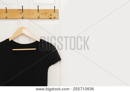 Black Woman Dress On Wooden Clothes Hanger On White Door With Copy Space. Isolated. Fashion And Dail