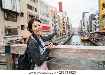 Charming Woman Pointing At Famous Landmark.