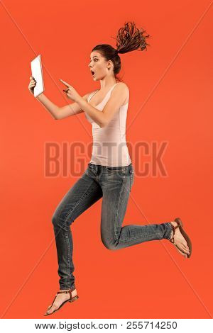 Jump Of Young Woman Over Blue Studio Background Using Laptop Or Tablet Gadget While Jumping. Runnin