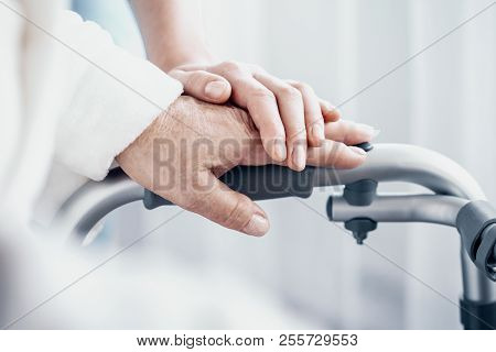 Close-up On Senior Person Hand On Walking Frame And Supporting Caregiver