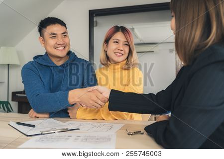Happy Young Asian Couple And Realtor Agent. Cheerful Young Man Signing Some Documents And Handshakin