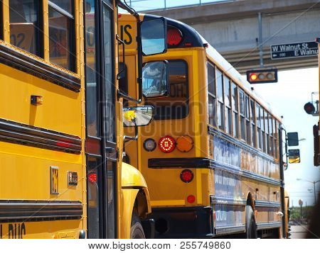 Buses Wait At A Street Light And Have A Rail Crossing On The Other Side. The Train Of Buses From The