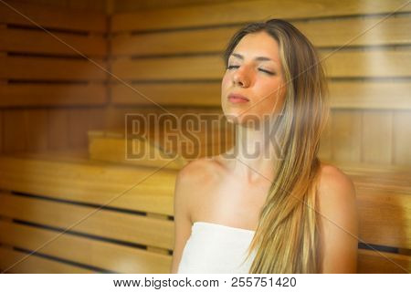 Beautiful woman having a sauna bath in a steam room