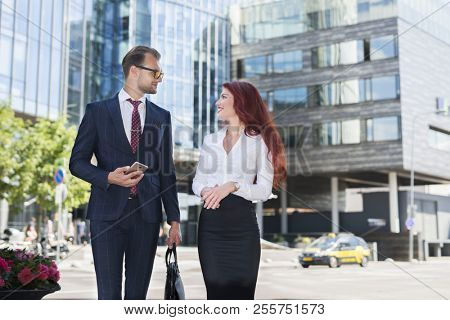 Business people walking and having a conversation in a city street