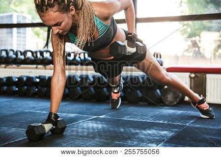 Image of fitness disabled sportsgirl with prosthesis in sportswear doing push ups with dumbbells in gym