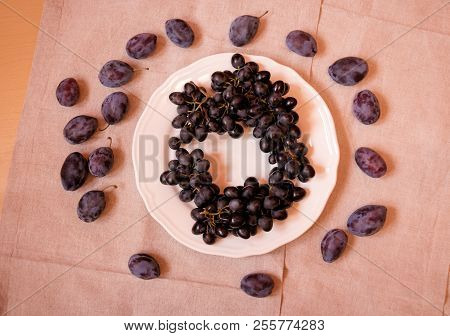 Black Grapes On Plate And Plums Near. Top View.