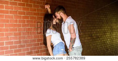 Desire and temptation. Girl and hipster strong desire feeling. Couple in love full of desire brick wall background. Couple find place to be alone. Couple enjoy intimacy moment without witnesses. poster