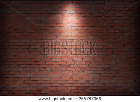 Abstract Old Brick Wall In The Dark With Spotlight Warm Light Tone. Brick Wall In Empty Room. Brick