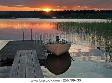 Small Boat Moored By Wooden Jetty At Peaceful Colorful Sunset By A Lake With Sky Reflections In Tran
