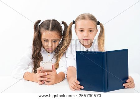 Reading Concept. Getting Information. Little Girls Reading Paper Book And Ebook In Smartphone. The R