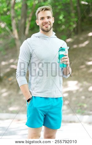 Man athlete hold bottle care hydration body after workout. Refreshing vitamin drink after great workout. Man athletic appearance holds water bottle. Athlete drink water after training in park. poster