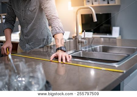 Young Asian Man Using Tape Measure For Measuring Granite Countertops On Modern Kitchen Counter In Sh
