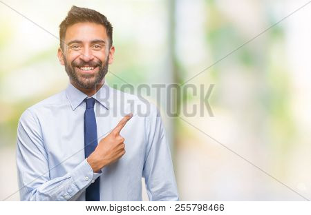 Adult hispanic business man over isolated background cheerful with a smile of face pointing with hand and finger up to the side with happy and natural expression on face looking at the camera.