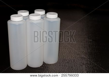 White Plastic Containers With Lids On Carbon Fiber Background
