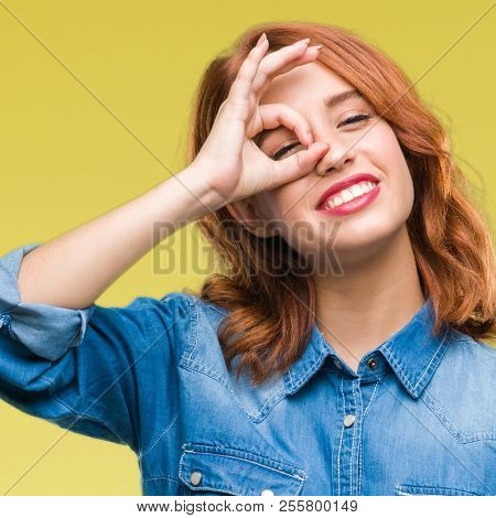 Young beautiful woman over isolated background doing ok gesture with hand smiling, eye looking through fingers with happy face.