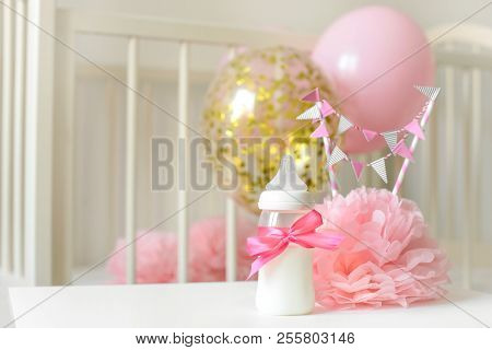 Baby Bottles With Breast Milk With Various Festive Paper Decor And Balloons In Front Of Baby Bedroom