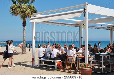 BARCELONA, SPAIN - APRIL 17, 2018: People sit at a taverna on the beach. The popular resort is the Capital of Catalonia.