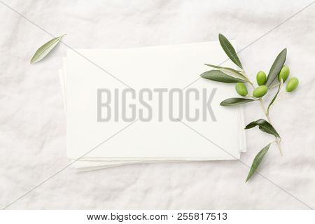 minimalist feminine styled invitation card mock-up (hand made paper) with fresh olive twig on a soft white linen background - perfect for wedding stationery. Flat lay / top view.