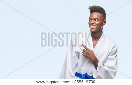 Young african american man over isolated background wearing kimono cheerful with a smile of face pointing with hand and finger up to the side with happy and natural expression on face