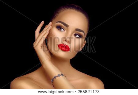 Beauty Brunette Woman with Perfect Makeup. Beautiful Professional Holiday Make-up. Red Lips, perfect eyebrows, face contouring. Beauty Girl's Face isolated on black background