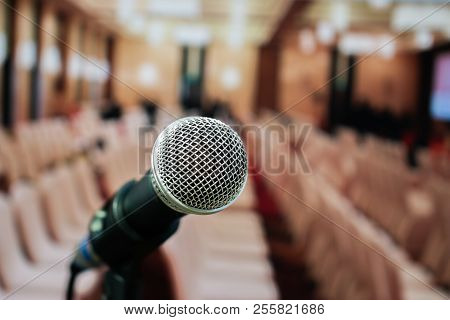 Microphones On Abstract Blurred Of Speech In Seminar Room Or Front Speaking Conference Hall Light, W