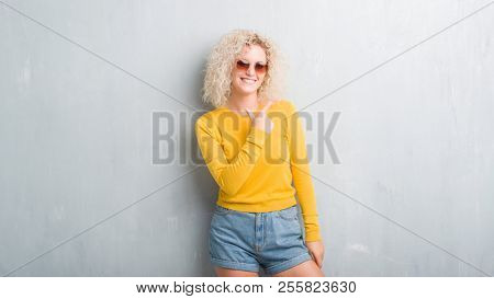 Young blonde woman with curly hair over grunge grey background cheerful with a smile of face pointing with hand and finger up to the side with happy and natural expression on face