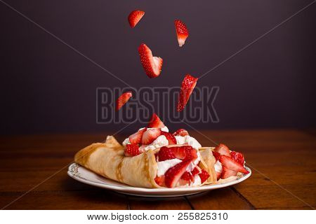 Delicious Crepes Filled With Strawberries And Whipped Cream With Strawberries Falling On Top Of The