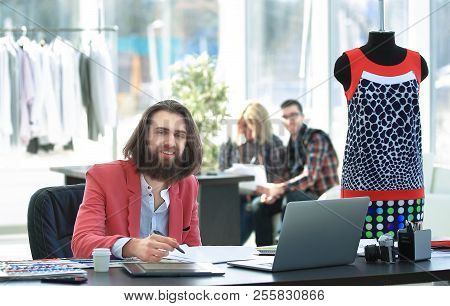 Professional Couturier Sitting At A Table In A Creative Studio