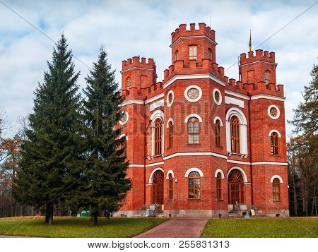 The facade of the historic building Arsenal with turrets, large windows, crenellated walls in English style in the Alexander Park in Tsarskoe Selo in the autumn on a clear day poster