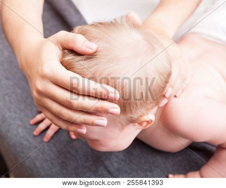 Seven month baby girl skull and neck are manipulated by osteopathic or chiropractic manual therapist